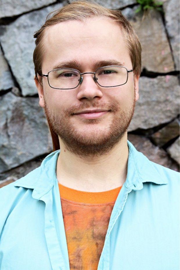 bild på sebastian som har håret bakåt uppsatt och rektangulära glasögon