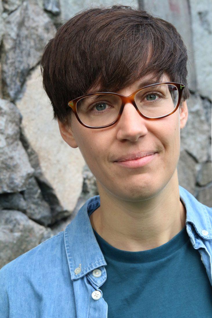 bild på sara som har kort mörkt hår och glasögon, ler mot kameran