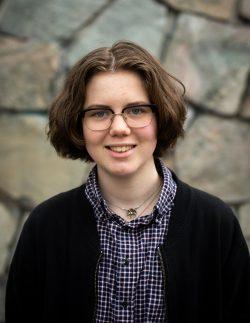 Syntolkning: Fotografi av Mayson. Hen har kort brunt hår, glasögon, halsband, en blårutig skjorta och en svart tröja. I bakgrunden syns en stenvägg.