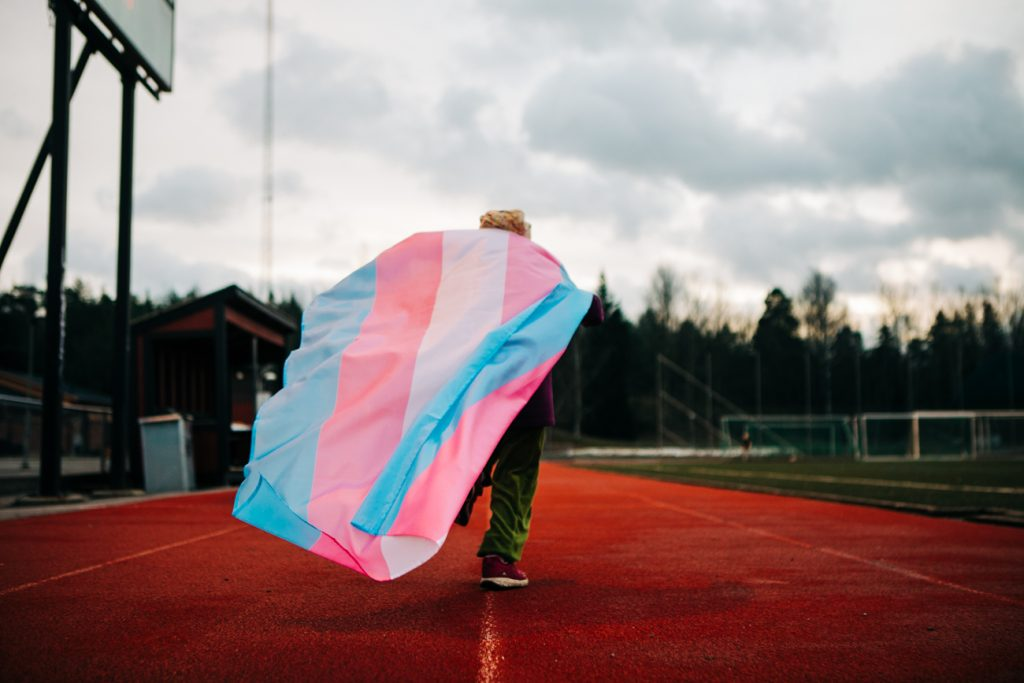 Syntolkning: Fotografi av en person som springer på en löpbanan med en transflagga. Personen har lila tröja, gröna byxor och röda skor. Transflaggan har fem ränder där första och femte randen är ljusblå, andra och fjärde randen är ljusrosa och tredje bandet vitt. I bakgrunden syns en idrottsplats, träd och en gråmulen himmel.