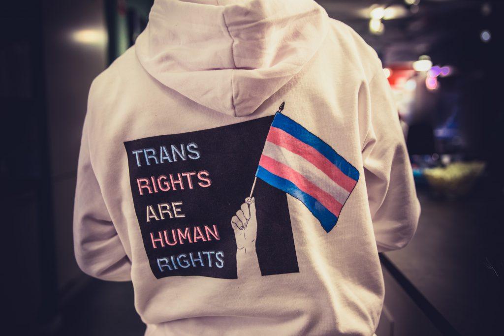 """Syntolkning: Fotografi på en person med vit hoodie. På ryggen är det ett tryck med texten """"Trans rights are human rights"""" och en transflagga mot en svart ruta."""
