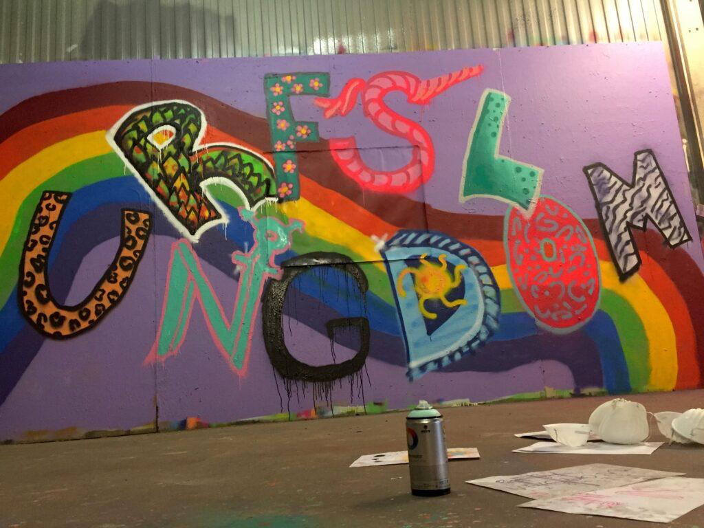 Syntolkning: Ett fotografi av en graffitimålning med RFSL Ungdoms namn.