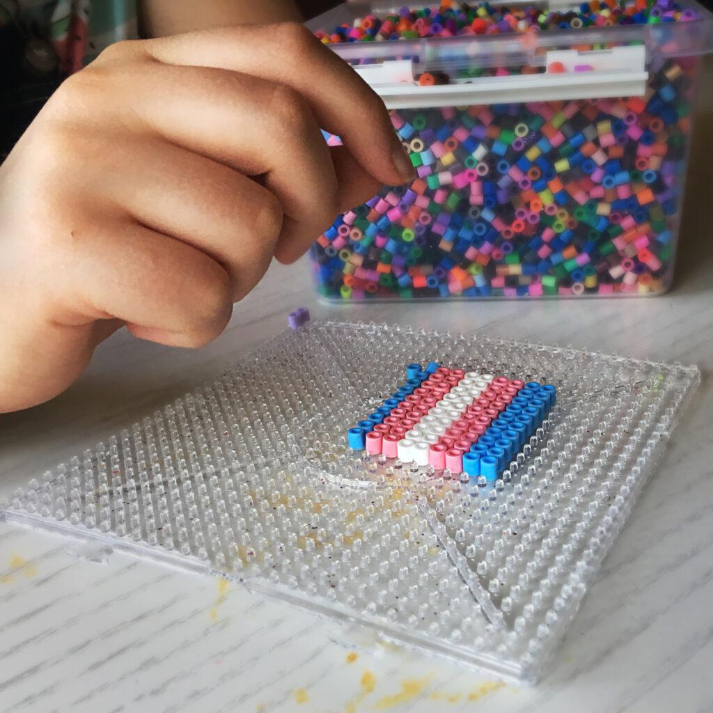 Syntolkning: En närbild på en person som lägger pärlor i form av transflaggan. I bakgrunden ses en låda med pärlor i olika färger.